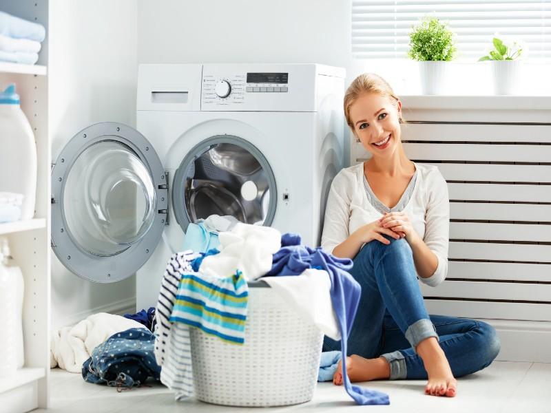 Χαρούμενη γυναικά δίπλα σε πλυντήριο ρούχων