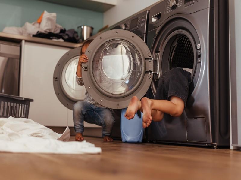 Ένα παιδί πίσω από πόρτα πλυντηρίου ρούχων & ένα παιδί στο εσωτερικό άδειου κάδου πλυντηρίου