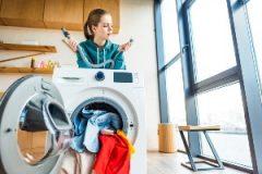 Προβληματισμένη γυναίκα πίσω από πλυντήριο ρούχων