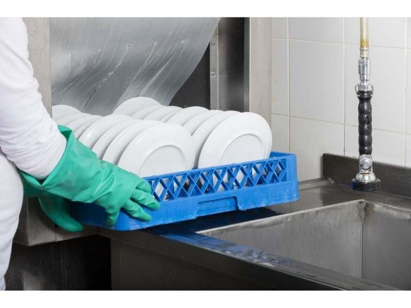 Χέρι βάζει παλέτα με πιάτα σε επαγγελματικό πλυντήριο πιάτων