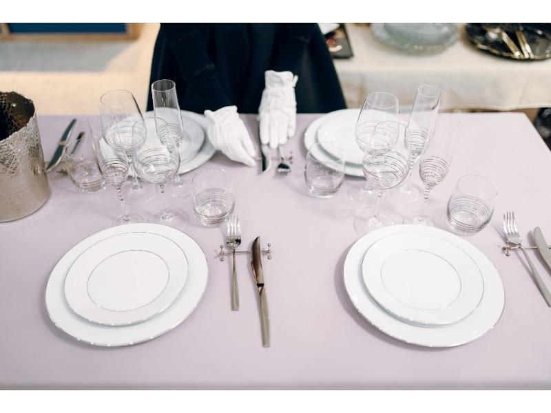 Χέρια με γάντια δίπλα σε πιάτα, μαχαιροπίρουνα & ποτήρια