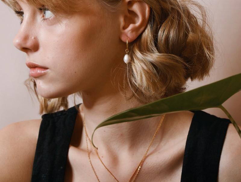 Νεαρή γυναίκα με σκουλαρίκι που περιέχει μαργαριτάρι