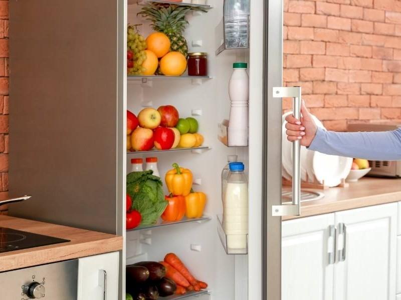 Χέρι ανοίγει πόρτα γεμάτου ψυγείου
